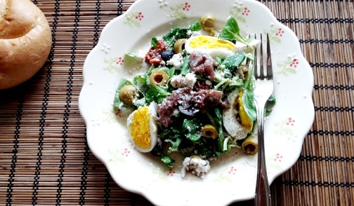 Sałatka z anchois, twarogiem i oliwkami posypana parmezanem
